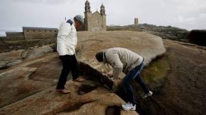 Os operarios de Loctite comproban os danos na pedra de abalar.