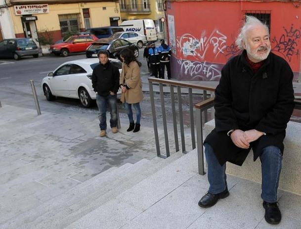 Mario López Rico espera para paralizar un despexo, coa policía ao fondo.